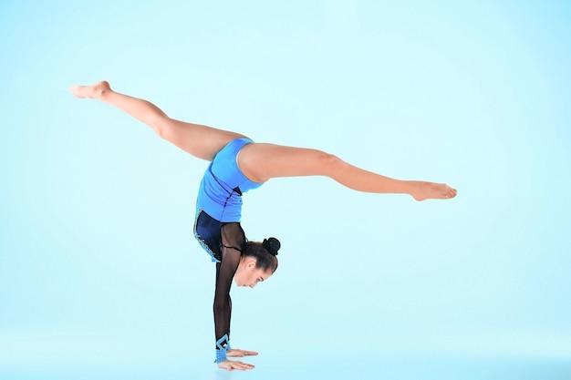 Девушка занимается гимнастикой на голубом