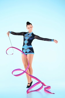 The girl doing gymnastics dance with colored ribbon on a blue space