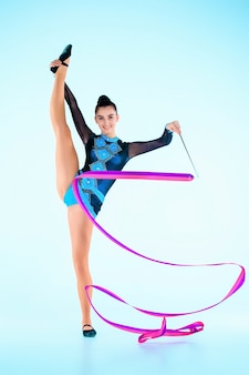 The girl doing gymnastics dance with colored ribbon on a blue wall
