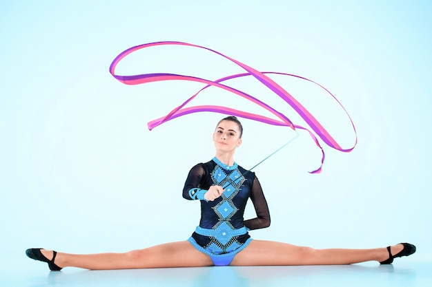 Girl doing gymnastics dance with colored ribbon on blue