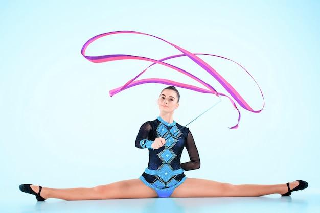 Девушка делает гимнастику танец с цветной лентой на синем