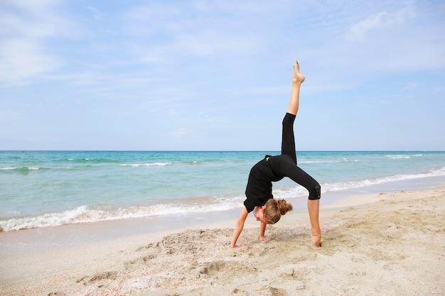 Девушка делает гимнастику на пляже.