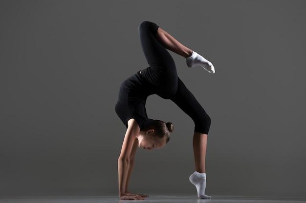 Девушка делает стойку на руках с ноги на полу