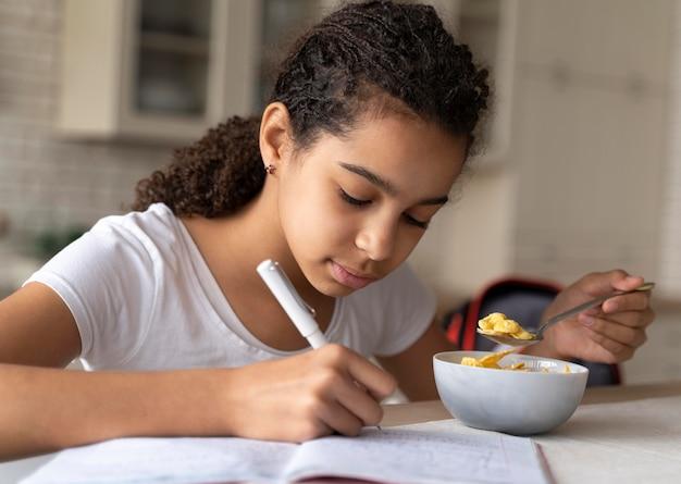 아침 식사하는 동안 그녀의 숙제를하는 여자