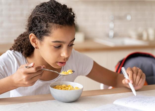Girl doing her homework while having breakfast