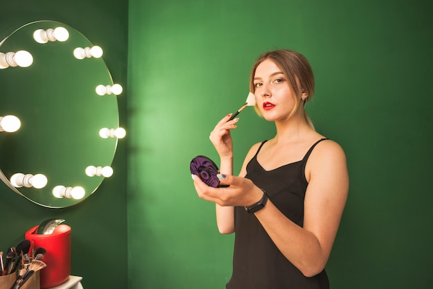 Girl doing her make up in a green room