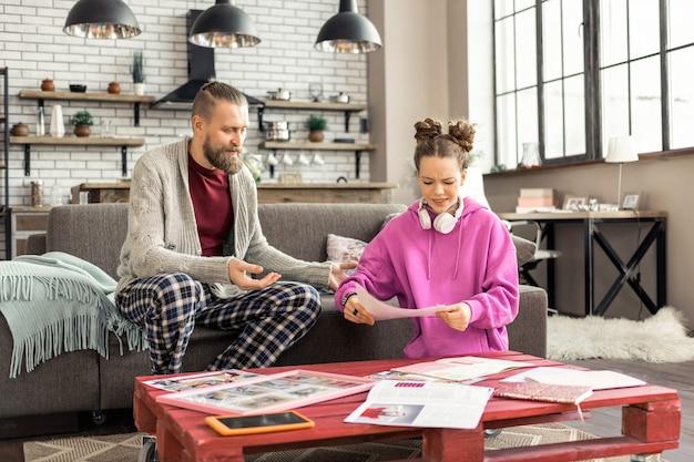 숙제를하는 소녀. 숙제를하는 동안 바쁜 느낌 그의 여자를보고 잠옷 바지를 입고 아버지