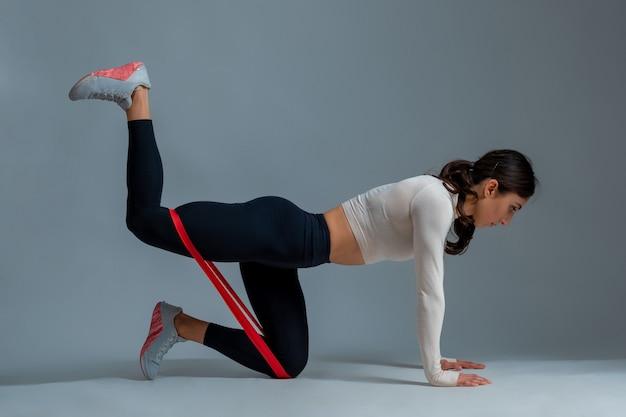 Девушка делает разгибание бедра на коленях с лентой сопротивления на серой стене