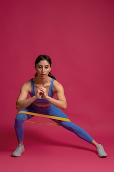 Girl doing lateral lunge with resistance band on maroon wall