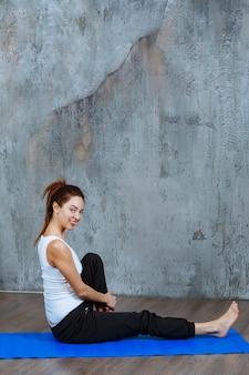 座った姿勢で脚と背中のストレッチトレーニングをしている女の子。
