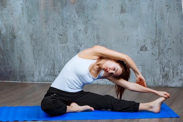 Ragazza che fa allenamento di allungamento della gamba e della schiena in posizione seduta.