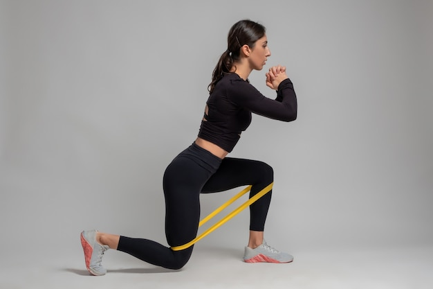 Girl doing lunge with resistance band on grey wall