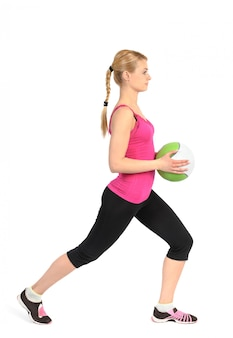 Girl doing lunges exercise with medicine ball
