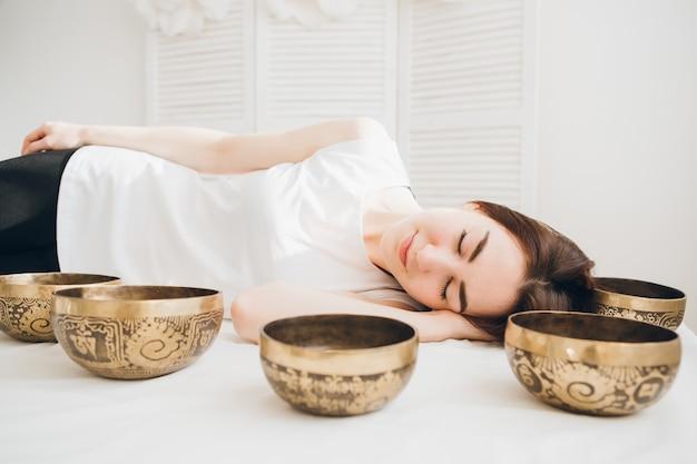 Девушка делает массаж терапии поющие чаши в спа