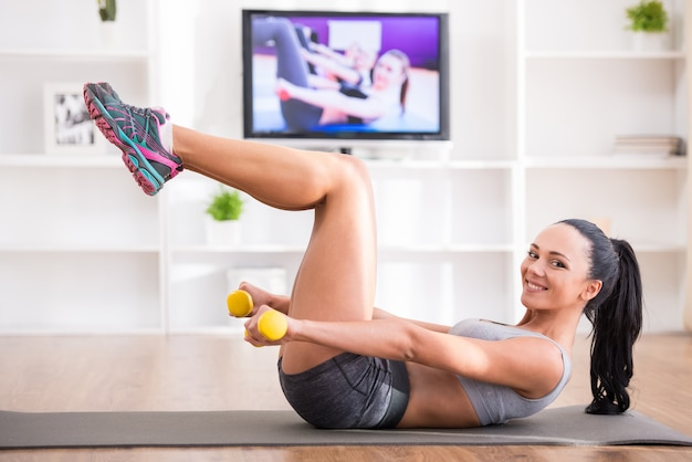 Girl doing press exercises at home.
