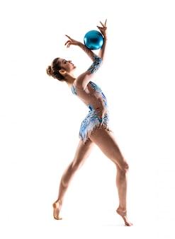 Девушка занимается художественной гимнастикой с мячом