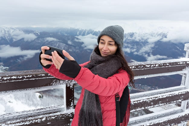 Girl doing selfie in the mountains in winter