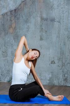 座った姿勢で肩と背中のストレッチトレーニングをしている女の子。