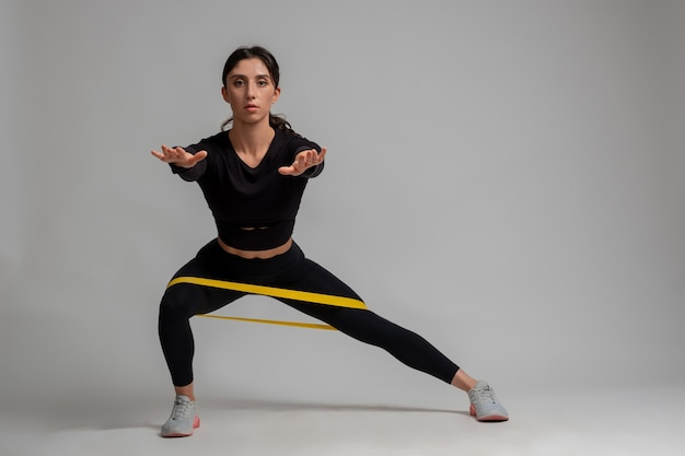 Girl doing side lunges with resistance band on grey wall