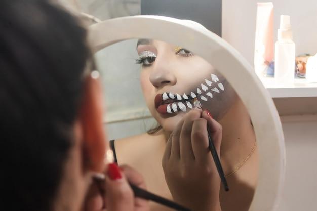 Girl doing skull teeth makeup for halloween in her room.