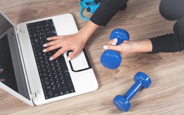 Девушка занимается спортом дома. просмотр онлайн-обучения