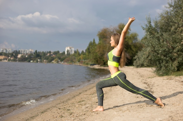 Girl doing sports on the beach. blonde doing yoga on the river bank.