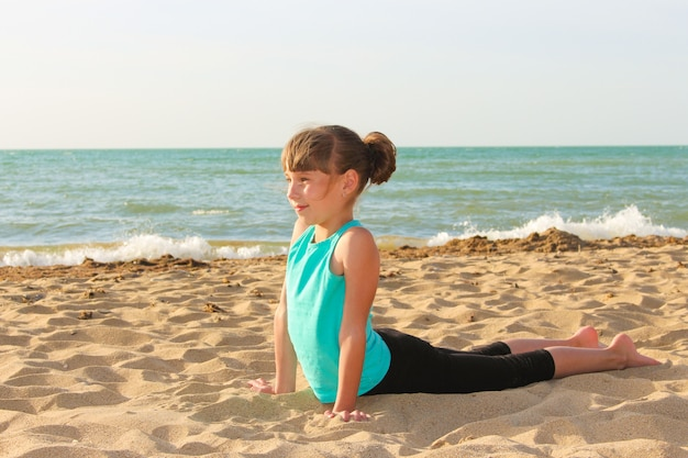Girl doing sports exercises on the beach