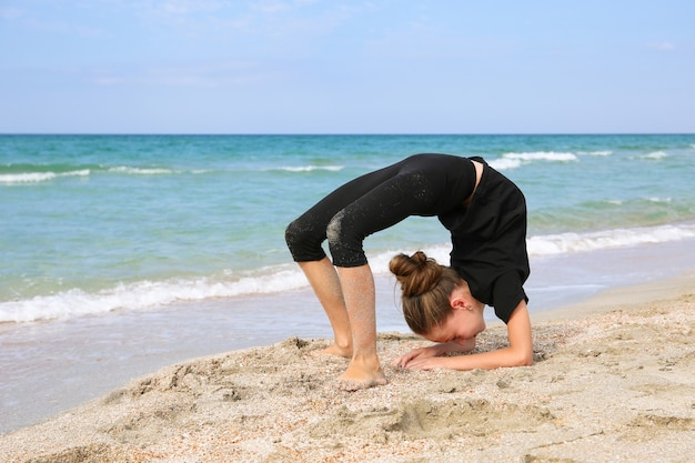 Девушка делает спортивные упражнения на пляже.