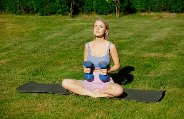 Girl doing sports exercises with dumbbells in the garden