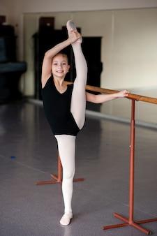 Girl doing stretching in ballet school.
