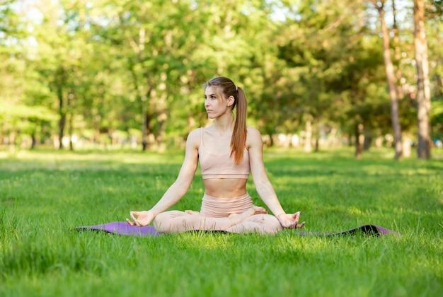 屋外ストレッチをしている女の子。ヨガの練習の若い女性
