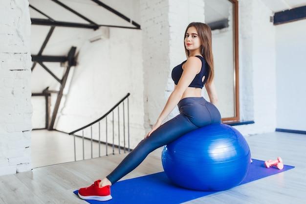 Девушка делает растяжку тела, сидя на спортивном мяче. концепция: образ жизни, фитнес, аэробика и здоровье.