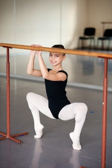 Девушка делает растяжку в балетной школе.