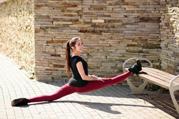 Девушка делает растяжку на улице. здоровый образ жизни и красивое тело.