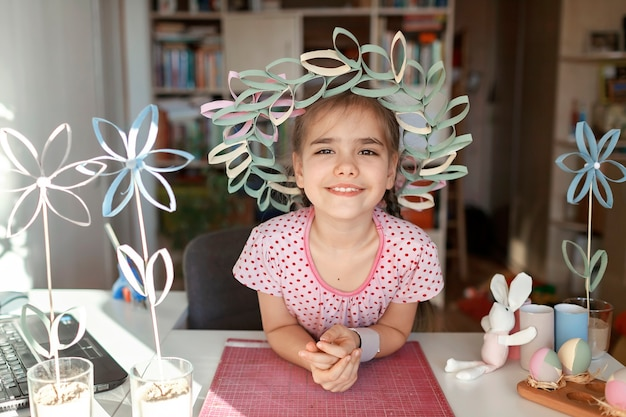 オンラインマスタークラスを介してトイレットペーパーチューブで花輪をしている女の子、ゼロウェイストイースターのお祝い