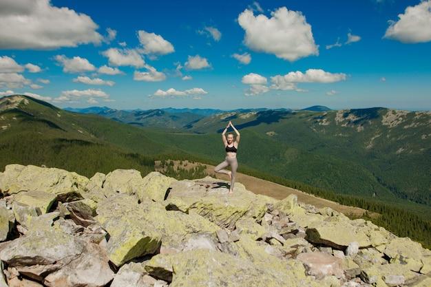 山の頂上でヨガの練習の蓮のポーズをしている女の子