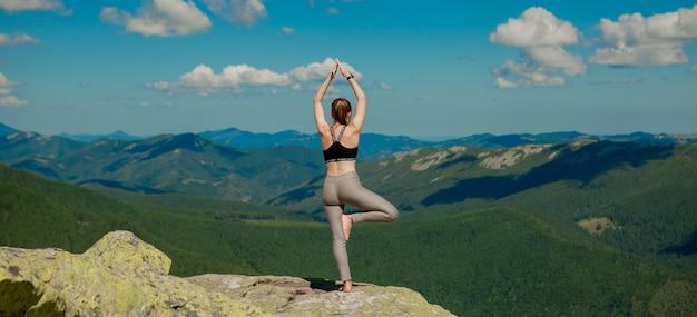 山の頂上でヨガエクササイズ蓮華座をしている女の子。