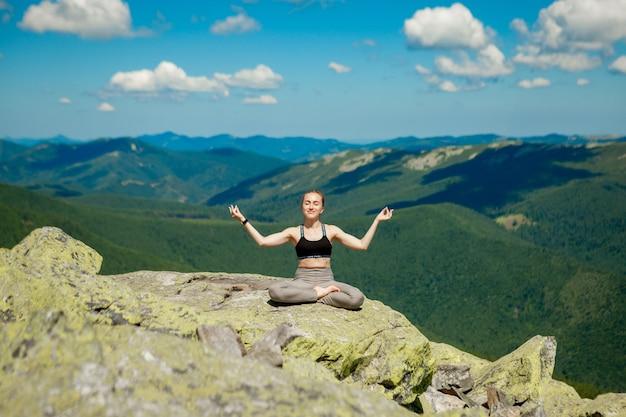 Девушка делает упражнения йоги позу лотоса на вершине горы.