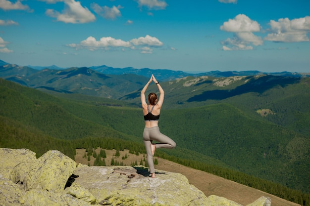 Girl doing yoga exercise lotus pose at the top of the mountain.