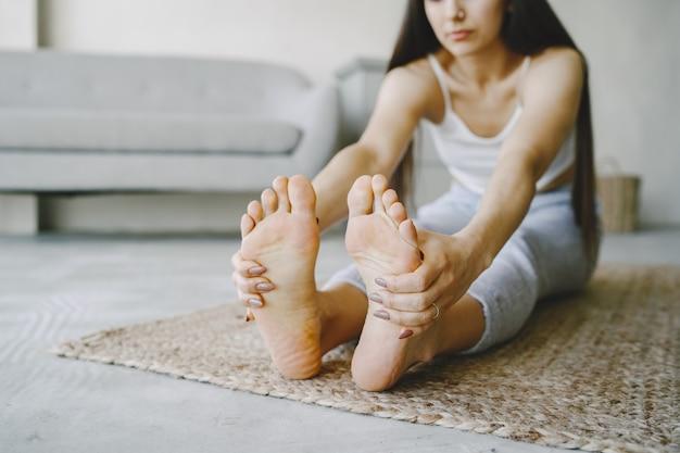Девушка делает упражнения йоги дома возле дивана и окна в спортивной одежде