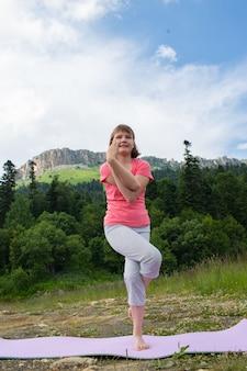 산을 배경으로 자연 속에서 요가를 하는 소녀