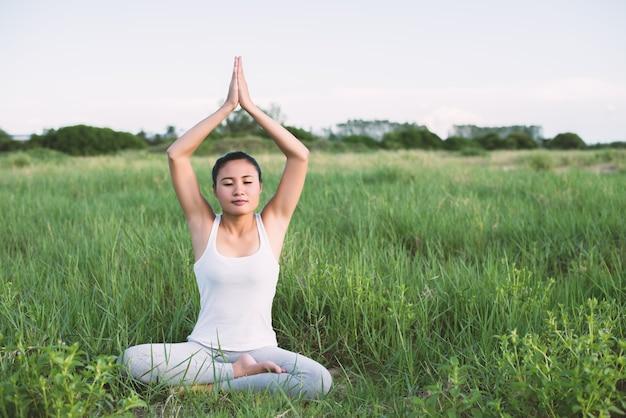 Девушка делает йогу в траве