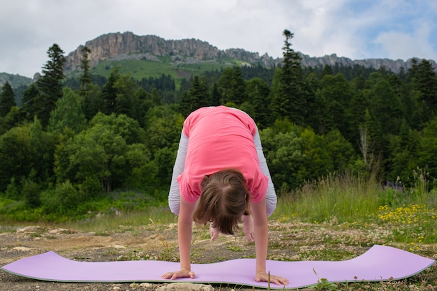 Girl doing yoga in nature on a background of mountains