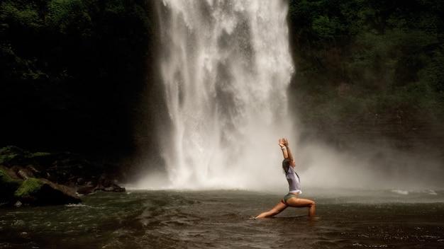 Ragazza che fa yoga in un paese aperto