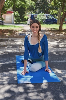 Girl doing yoga posture on the street. girl smiling and looking at camera