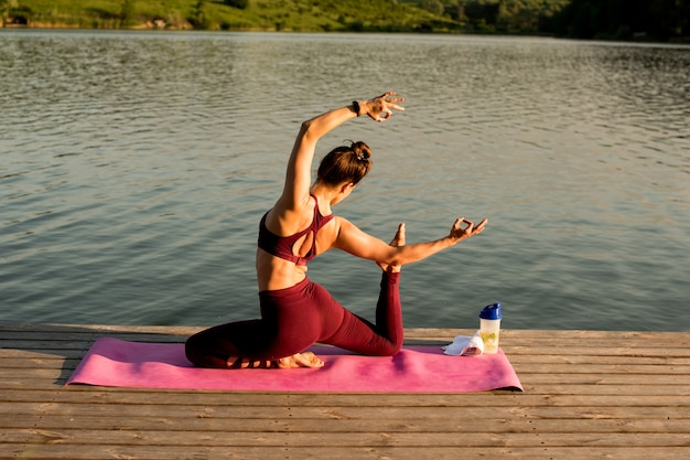 Girl doing yoga on the river bank. she does yoga exercises, does asanas.