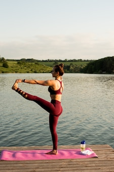 Girl doing yoga on the river bank. she stretching her leg