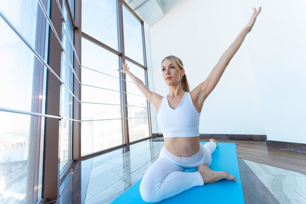 Girl doing yoga while sitting in pigeon pose with raised arms