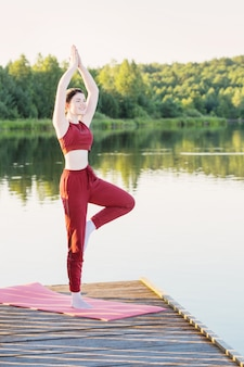 Girl doing yoga on wooden pier by lake in summer