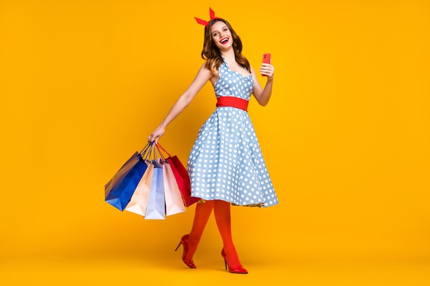 Girl in dotted dress hold shopping bags and smartphone on yellow background
